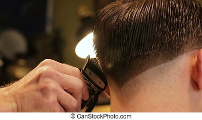 Professional barber in barbershop does haircut with clipper, close-up view