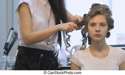 Professional barber makes hairstyle for the model -...