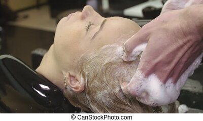Professional barber rub in shampoo in hair of blonde young girl in barbershop. Massage of head
