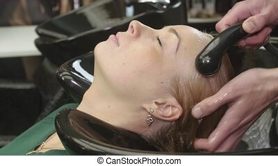 Professional barber wash hair of blonde young girl by water in beauty saloon. Massage of head