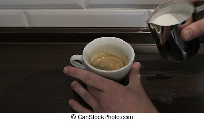 Professional barista pouring a cappuccino in a busy coffee...