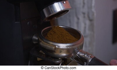 Professional barista worker man using grinder machine to ...