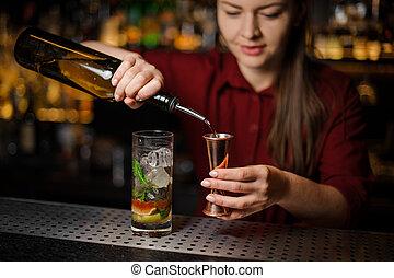 professional barmaid prepares a mojito, adding dark rum
