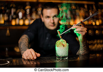 Professional bartender adding to a glass with dried orange and ice a smoked cinnamon with tweezers