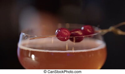 Professional bartender decorating cocktail with raspberry