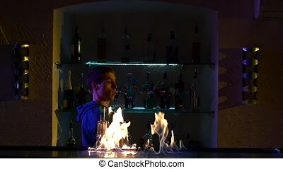 Professional bartender making cool, amazing tricks with two bottles standing behind the bar, catching on arm, throwing up, fire show, slow motion