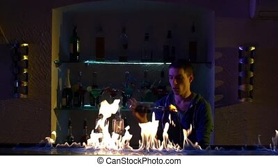 Professional bartender making cool, amazing tricks with two glasses, shaker and bottle standing behind the bar, catching on elbow, throwing up, fire show, slow motion