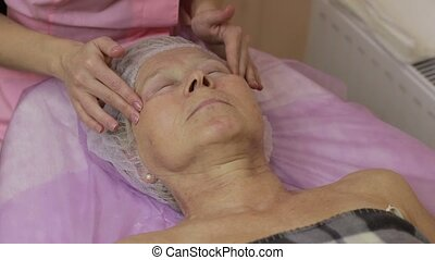 Professional beautician massaging human face - Closeup arms...