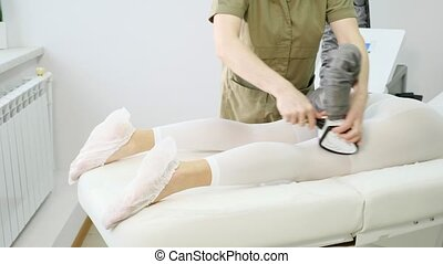 professional beautician practices procedure of lipomassage with special electric device on visitor legs in salon