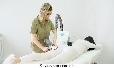professional beautician practices procedure of massage with special electric device on visitor back and legs in salon