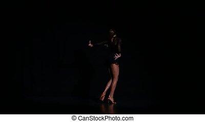 Professional beautiful dancer in a studio on a dark background