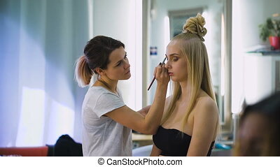 Professional Beauty judge and stylist at work. For a spectacular top models make a bright, expressive makeup. Stylish hairstyle and image