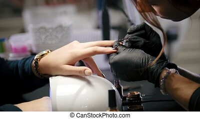 Professional beauty salon - manicure master doing cosmetic procedure for attractive young woman
