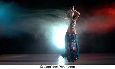 Professional belly dancer in a blue stage costume dancing in smoke, on red, blue, slow motion