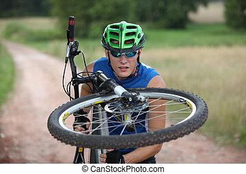 Professional biker - close up - Biker looking at front wheel...