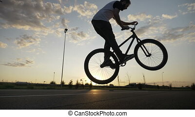 Professional biker jumping and flipping the handlebar on his...