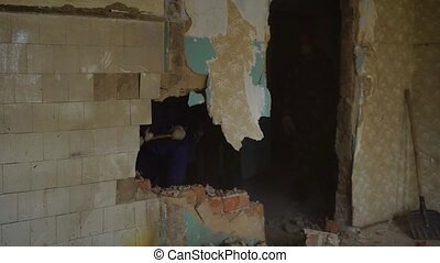 Professional builder demolishing wallk in an old building...