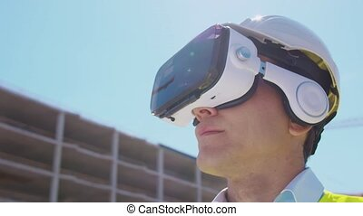 Professional builder in VR helmet standing in front of construction site and using virtual and augmented reality technologies. Office building and crane background. Real estate and investment concepts.