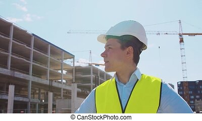Professional builder standing in front of construction site...