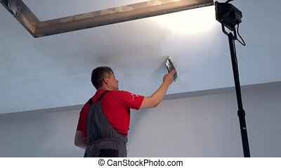 Professional builder with trowel plaster ceiling. Static...