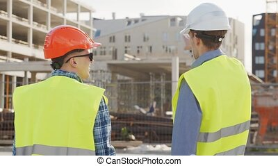 Professional builders standing in front of construction site...