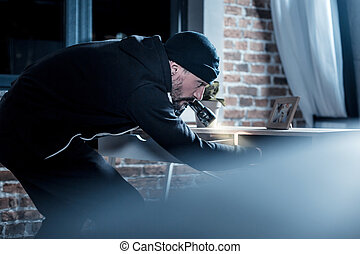 Professional burglar looking for documents in the table