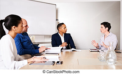 Professional business meeting between 4 educated, racially diverse entrepreneurs
