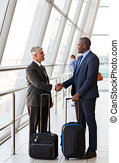 businesspeople handshaking at airport