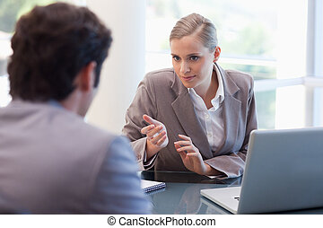 Professional businesswoman receiving a customer in her ...