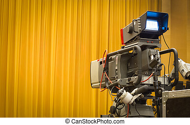 Professional camera and closed yellow curtains.