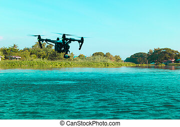 Professional camera drone flying on river.