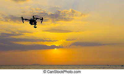 Professional camera drone flying on sea.