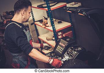 Professional car mechanic balancing car wheel on balancer in...