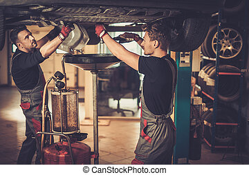 Professional car mechanic changing motor oil in automobile...