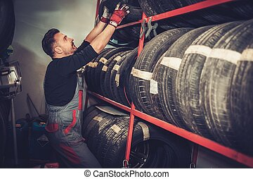 Professional car mechanic choosing new tire in auto repair service.