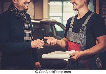 Professional car mechanic giving client keys to his repaired...