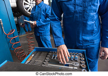 Professional car mechanic standing near set with tools