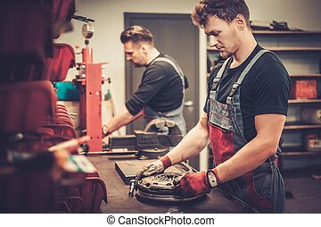 Professional car mechanics working at work table in auto repair service.