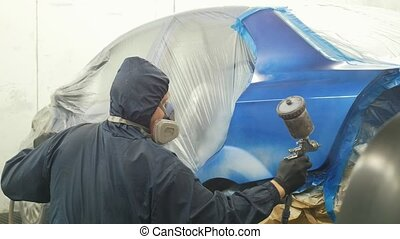 Professional car painter in vehicle workshop, close up