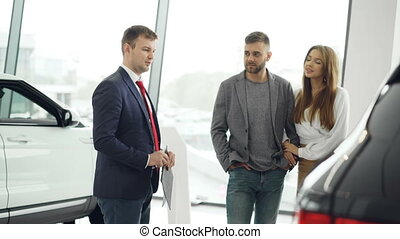 Professional car salesman is telling interested buyers...