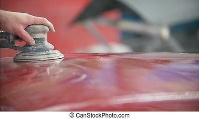 Professional car service - a worker polishes red automobile...