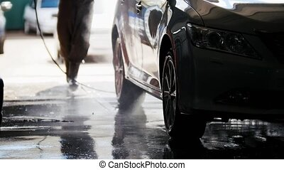 Professional car washing in auto service, telephoto