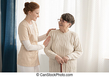 Professional caregiver assisting elderly woman