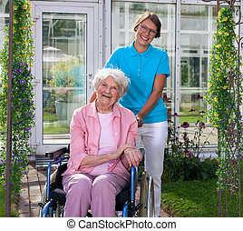 Professional carer behind happy elderly woman