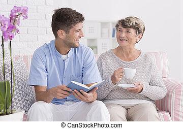 Professional carer reading to senior