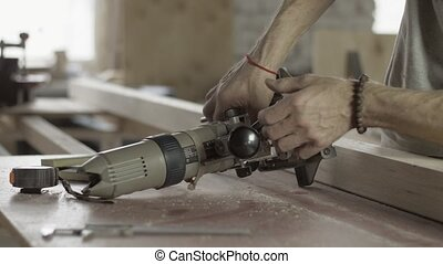 Professional carpenter adjusts plunge router by wrench....