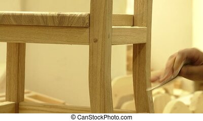 Professional carpenter sanding wooden chair with sandpaper...