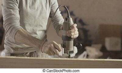 Professional carpenter shakes sawdust from plunge router....