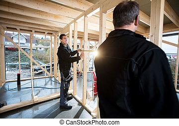 Professional Carpenters Measuring Wooden Pillars At Site