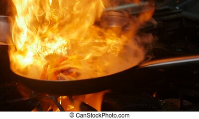 Professional chef and fire. Cooking vegetables and food over...